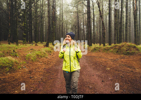 Cheerful beautiful caucasian middle age woman doing trekking outdoor activity in the forest ina rainy day - adventure lifestyle for people love freedo - Stock Image