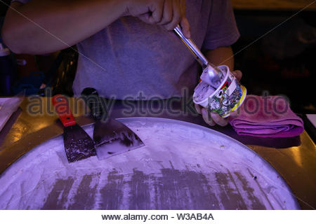 Woman hand making ice cream on round cold plate - Stock Image