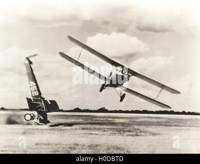 Biplane flying past crash on field - Stock Image