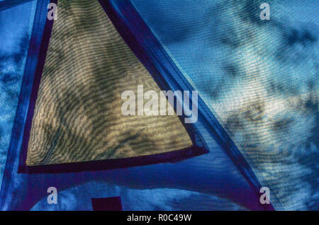 Tent interior looking outwards through screening material towards setting sun, with trees throwing leaf shadows on tent side. - Stock Image