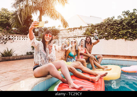 Group of happy friends making pool party taking selfie with mobile smartphone - Young people having fun in exclusive summer tropical vacation - Stock Image