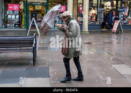 Bath, UK. 8th February, 2019. As storm Eric brings gales and heavy rain across the UK a pedestrian is pictured in the centre of Bath struggling with an umbrella as she braves the heavy rain and wind. Credit: Lynchpics/Alamy Live News - Stock Image
