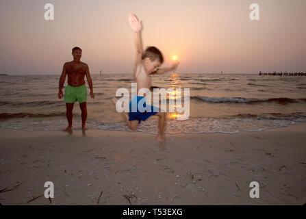 Florida Gulf Coast Tampa Bay Bahia Beach boy leaps near surf sunset - Stock Image