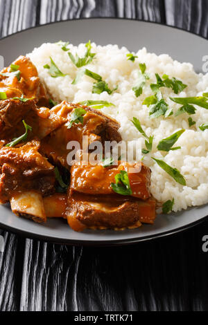 Stewed ribs in a spicy sauce served with white rice close-up on a plate. vertical - Stock Image