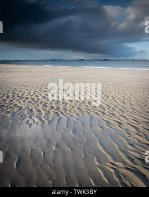 storm clouds over a sandy beach - Stock Image