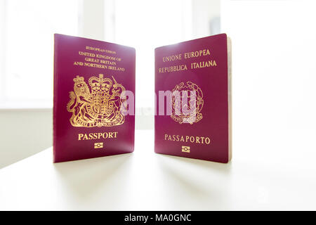British and Italian passports standing next to each other, with white light exploding in the background. - Stock Image