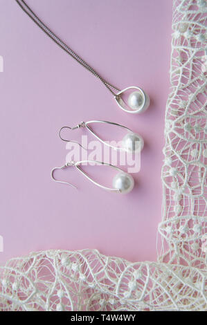 Beautiful silver shiny pearl jewelry, trendy glamorous earrings, chain on pink purple background with exquisite lace. Lay Flat, top view, copy the loc - Stock Image