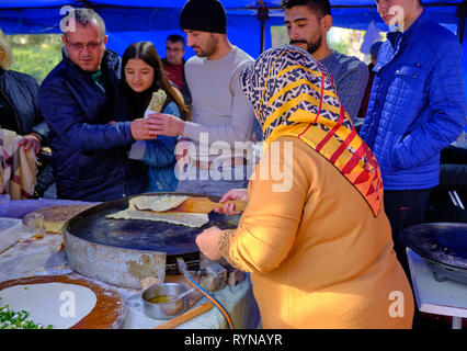 Local woman with head scarf preparing turkish pancakes (gozleme) for customers at a fair in Antalya, Turkey - December 29, 2018 - Stock Image