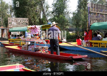 Man Selling Dolls Souveniers Snacks and Blankets on a Boat on the Canals of the Floating Gardens of Xochimilco Mexico - Stock Image