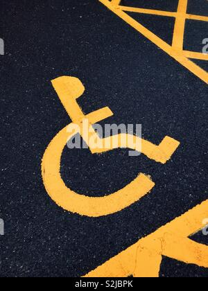 The yellow logo sign of a person in a wheelchair. This car parking area is reserved for people who have transportation disabilities. Photo Credit - © COLIN HOSKINS. - Stock Image