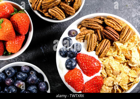 Healthy Breakfast of Cereals With Fresh Fruit and Nuts, Corn Flakes, Pecan Nuts, Strawberries, Blueberries and Yogurt. - Stock Image
