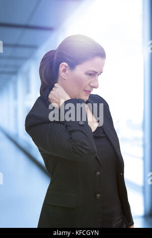 Middle aged woman with chronic pain syndrome fibromyalgia suffering from acute neckache - Stock Image