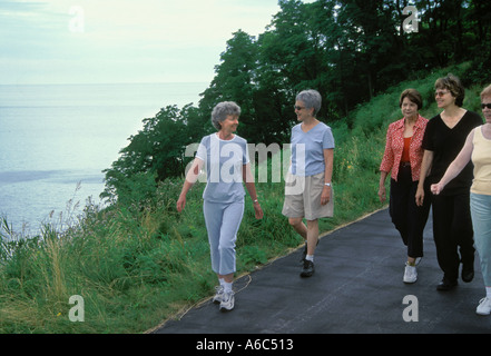 Senior Caucasian women walk and chat as a group together on bluff above lake  in Northwest America - Stock Image