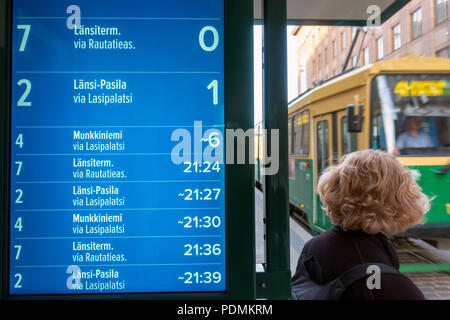 Electronic timetable display showing estimated arrival times of trams with tram arriving at tram stop on Aleksanterinkatu Street in Helsinki Finland - Stock Image