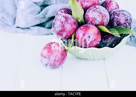Freshly picked homegrorwn organic plums in a petty green bowl. Room for text. - Stock Image