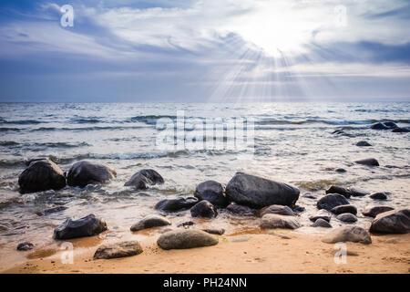 Sunset over rocky seacoast - Stock Image