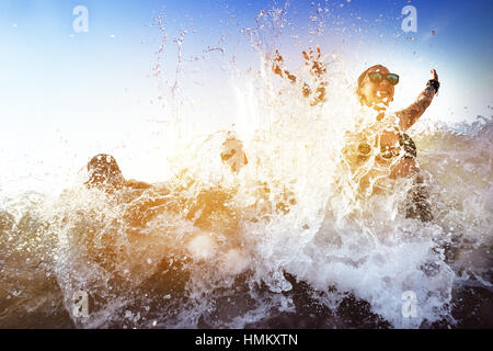 Happy friends beach sunset waves - Stock Image