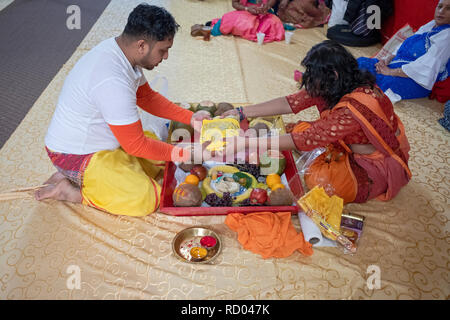 A Hindu priestess and devout worshipper prepare offerings to the deities prior to a service at a temple in Ozone Park Queens, New York City. - Stock Image