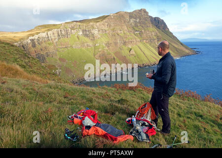Mull, UK. 6th October 2018. Hill walker enjoying a well earned sandwich and coffee looking the shoreline below where he'd just climbed up from and keeping an eye on the rain clouds appearing, after a beautiful autumnal day, over Binnein Gorrie known locally as 'Gorrie's Leap' in a remote part of the Ross of Mull on the Hebridean island of Mull. Credit: PictureScotland/Alamy Live News - Stock Image