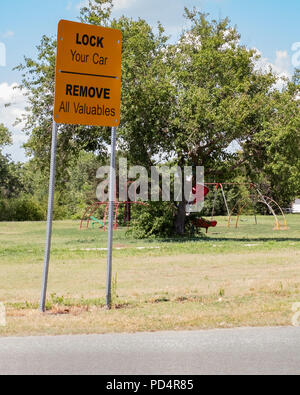 A sign warning people to lock their cars and remove valuables in a public park in Wichita, Kansas, USA. - Stock Image