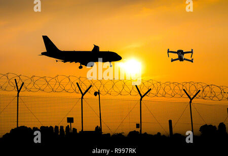 Unmanned drone flying over security fence at airport while commercial airplane prepares for landing, leading to possible collision - digital composite - Stock Image