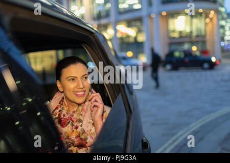 Smiling businesswoman talking on smart phone in crowdsourced taxi at night - Stock Image