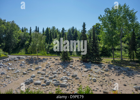 Railway track cutting through a forest in a mountainous landscape - Stock Image