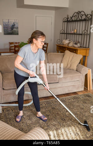 Woman cleaning carpet with vacuum in living room in a nice home. - Stock Image