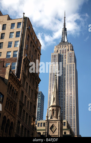 Empire State Building rising above the lower buildings of midtown, New York, NY, USA - Stock Image