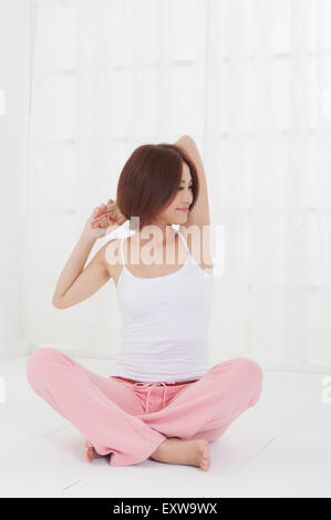 Young woman sitting on the floor and looking away with smile, - Stock Image