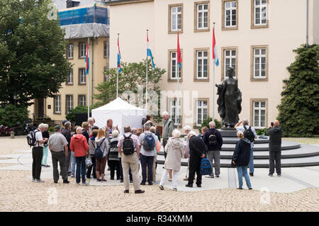 A group of tourists with a tour guide at the Statue of Grand Duchess Charlotte, Clairfontaine Square, Luxembourg city, Luxembourg, Europe - Stock Image