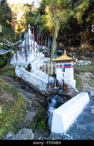 Water-turned prayer wheel and stupa beside road between Dochu La and Metshina in western Bhutan - Stock Image