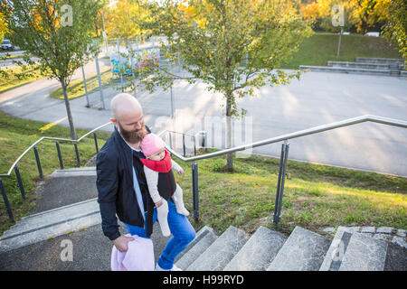 Father with baby girl in baby carrier walking up steps - Stock Image