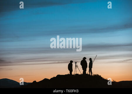 Group of silhouettes of photographers against sunset sky - Stock Image