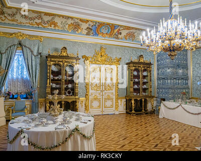 18 September 2018: St Petersburg, Russia - An ornate room in the Peterhof Palace, with chandelier and table set for tea. - Stock Image