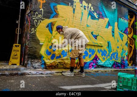 Graffiti artist at work in Melbourne laneway - Stock Image