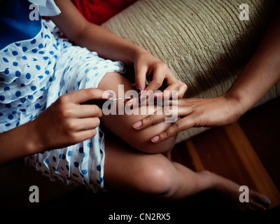 Young girl applies nail polish to her mother's nails. - Stock Image