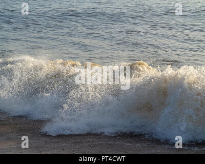 Waves breaking on the shoreline with some spray and foam in the foreground - Stock Image
