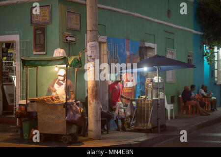 A barbecue on the colourful streets of Getsemani at dusk, Cartagena, Colombia, South America - Stock Image