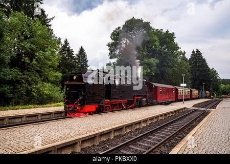 Old steam locomotive leaving the train station with smoke coming out of the chimney - Stock Image