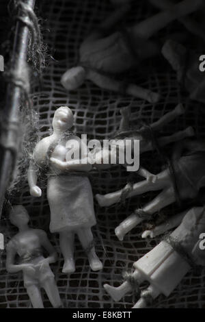 Family figurines tied to a piece of cloth. - Stock Image