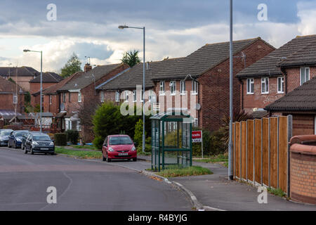 A typical town residential street with cars, redbrick houses, streetlights, & a bus stop but no peoplen on an overcast day.  Trowbridge Wiltshire UK - Stock Image