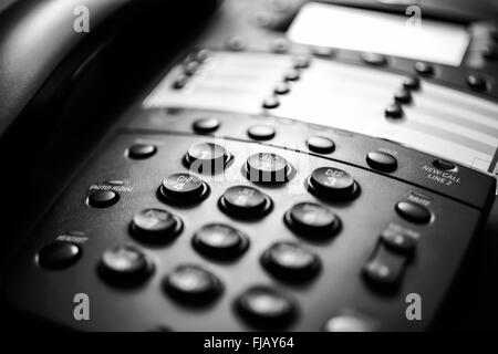 Modern black business landline telephone with number keypad close-up. - Stock Image