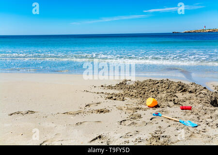 Crystal clear blue water of  Mediterranean sea on St.Croix Martigues white sandy beach and colorful kids beach toys, Provence, France, vacation destin - Stock Image