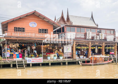 Amphawa, Thailand - 7th October 2018: Tourists shopping by the river. A floating market is held every weekend. - Stock Image