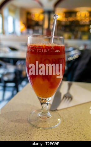 Refreshing fruit drink in an Italian Restaurant made from fresh oranges and raspberries. - Stock Image