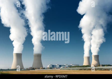 four power plant cooling towers steaming on dark blue sky background - Stock Image