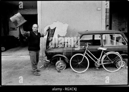 Casole d'Elsa, Tuscany, Italy. 1990. Scanned in 2019 Street and cafe bar life in the small hill top town of Casole d'Elsa in Tuscany Italy. Man with car neading some attention. - Stock Image