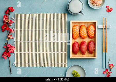 Nigiri sushi with salmon and tuna served on bamboo plate  with chopsticks, soy sause, wasabi and ginger on blue background. Delicious traditional Japa - Stock Image