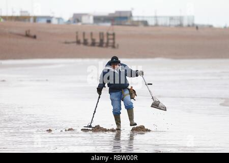 Hastings, East Sussex, UK. 12 Jan, 2019. UK Weather: Winter weather with a slight breeze in the air that is expected to last throughout the day as a few people take a morning stroll around the seafront as the tide is out. A metal detectorist tries his luck on the beach. © Paul Lawrenson 2018, Photo Credit: Paul Lawrenson / Alamy Live News - Stock Image